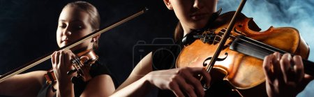Photo for Attractive musicians playing on violins on dark stage with smoke, website header - Royalty Free Image