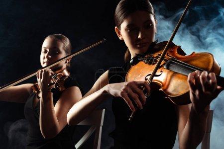 Photo pour Beaux musiciens jouant sur des violons sur scène sombre avec de la fumée - image libre de droit
