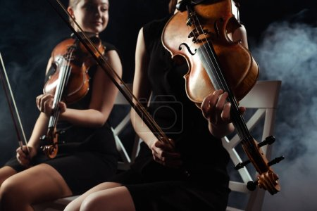 cropped view of attractive musicians playing on violins on dark stage with smoke