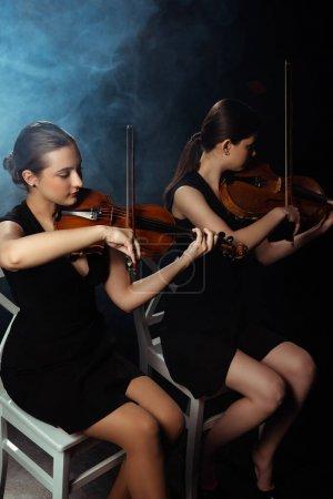 Photo pour Musiciens professionnels attrayants jouant sur des violons sur scène sombre avec de la fumée - image libre de droit