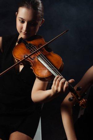 Photo pour De beaux musiciens professionnels jouant de la musique classique sur violons sur scène sombre - image libre de droit