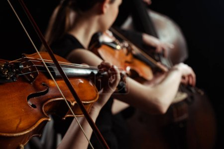 Photo pour Vue recadrée de musiciennes professionnelles jouant sur violons sur scène sombre, mise au point sélective - image libre de droit
