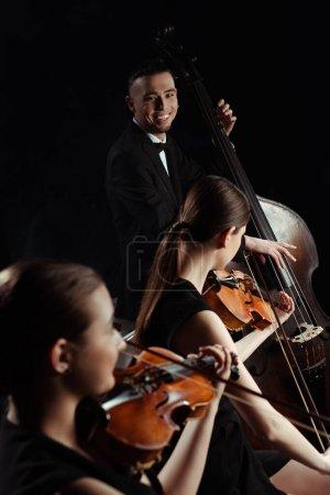 Photo pour Heureux musiciens professionnels jouant sur contrebasse et violons isolés sur noir - image libre de droit