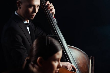 Photo for Professional musicians playing on violin and contrabass on dark stage - Royalty Free Image