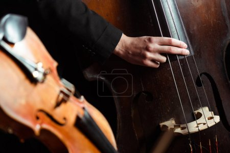 Photo for Professional musician playing on double bass on dark stage with selective focus of violin - Royalty Free Image