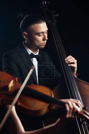 Photo pour Deux musiciens professionnels jouant du violon et de la contrebasse sur scène sombre - image libre de droit
