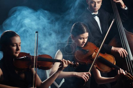 Photo for Trio of musicians playing on violins and contrabass on dark stage with smoke - Royalty Free Image