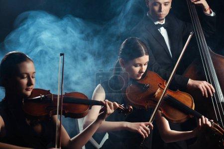 Foto de Trío de músicos tocando violines y contrabajo en escenario oscuro con humo - Imagen libre de derechos