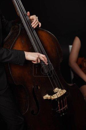 Photo pour Vue partielle de musiciens professionnels jouant du violon et de la contrebasse sur scène sombre - image libre de droit