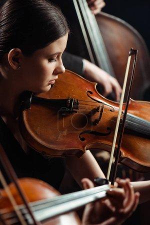Photo pour Musiciens professionnels jouant de la musique classique sur scène sombre - image libre de droit