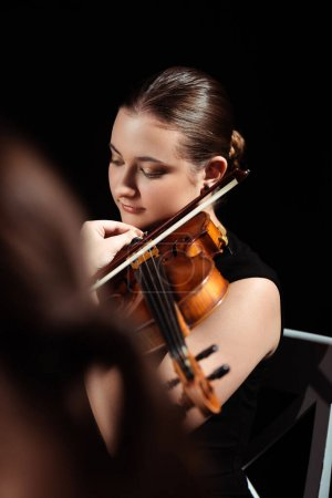 Photo for Attractive female musician playing on violin on dark stage - Royalty Free Image