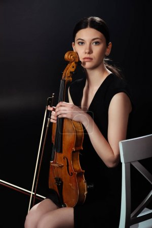 Photo for Attractive female musician holding violin on dark stage - Royalty Free Image
