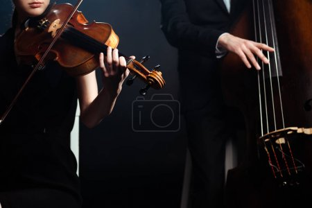 cropped view of professional musicians playing on violin and contrabass on dark stage