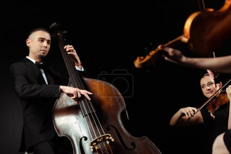 Photo for Professional musicians playing on double bass and violins isolated on black - Royalty Free Image