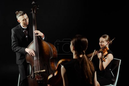 Photo for Trio of musicians playing on double bass and violins isolated on black - Royalty Free Image
