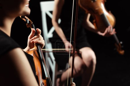 Photo for Partial view of female professional musicians playing on violins on dark stage, selective focus - Royalty Free Image