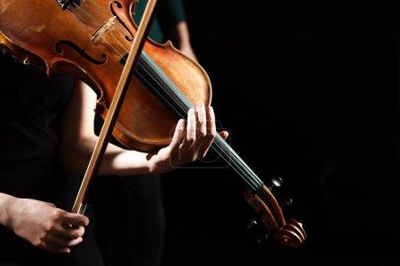 Photo pour Vue partielle d'une musicienne exécutant une symphonie sur violon isolé sur noir - image libre de droit