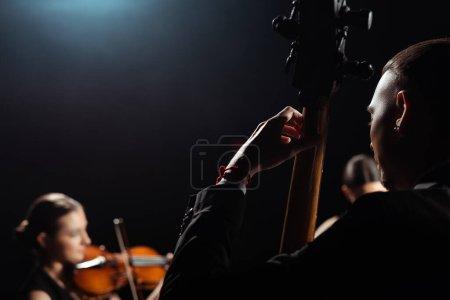 Photo pour Trio de musiciens professionnels jouant sur des instruments de musique sur scène sombre - image libre de droit