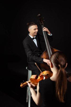 Photo pour Musiciens professionnels joyeux jouant sur violon et contrebasse sur scène sombre - image libre de droit