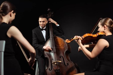 Photo for Trio of happy musicians playing on double bass and violins isolated on black - Royalty Free Image