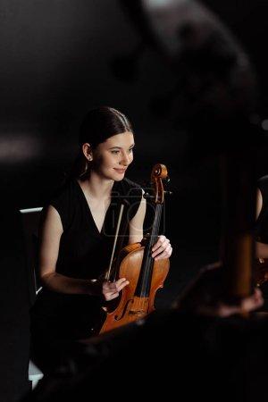 Photo pour Heureuse musicienne tenant violon sur scène sombre - image libre de droit