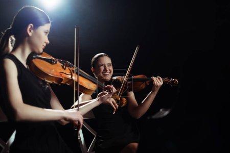 Photo pour Musiciens féminines riantes jouant sur violons sur scène sombre avec contre-jour - image libre de droit