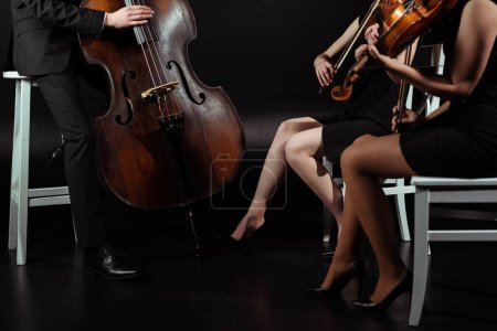 Photo for Cropped view of professional musicians playing on violins and contrabass on dark stage - Royalty Free Image