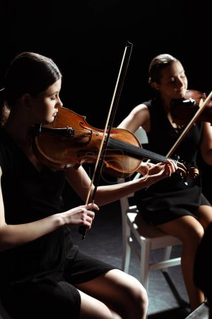 Photo for Attractive professional female musicians playing classical music on violins on dark stage - Royalty Free Image