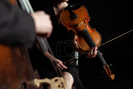 Photo for Partial view of professional musicians playing on violin and double bass on dark stage, selective focus - Royalty Free Image