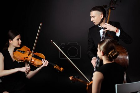 trio of professional musicians playing on musical instruments on dark stage