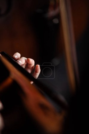 Photo for Cropped view of professional musician playing on violin on dark stage - Royalty Free Image