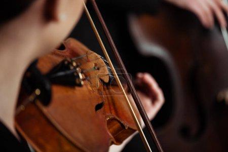 Photo pour Vue recadrée de musiciens professionnels jouant sur des instruments de musique sur scène sombre, mise au point sélective - image libre de droit