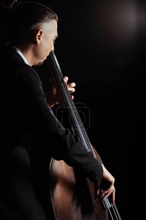 professional young musician playing on contrabass on dark stage
