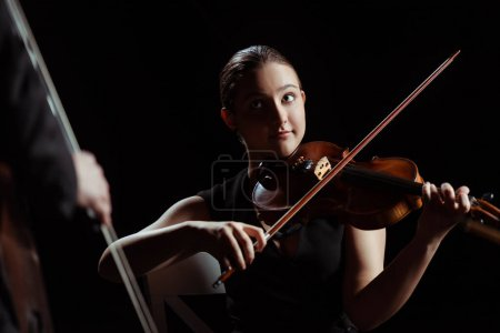 professional musicians playing on violin and contrabass on dark stage