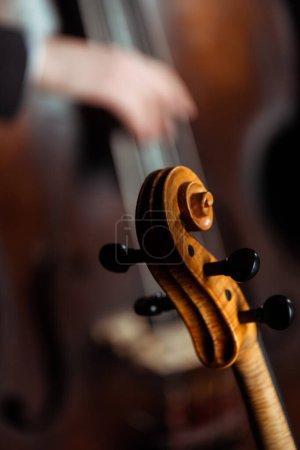 Photo pour Vue recadrée de musiciens professionnels jouant du violon et de la contrebasse sur scène sombre, mise au point sélective - image libre de droit