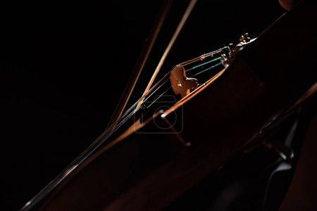 Photo pour Vue partielle du musicien jouant de la symphonie sur violon isolé sur noir - image libre de droit