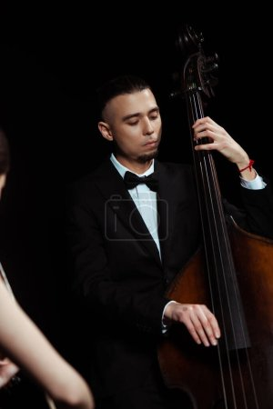 Photo for Focused professional musicians playing on violin and contrabass on dark stage - Royalty Free Image