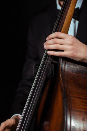 Photo for Cropped view of male musician playing on contrabass isolated on black - Royalty Free Image