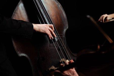 Photo pour Vue recadrée de musiciens professionnels jouant du violon et de la contrebasse sur scène sombre - image libre de droit