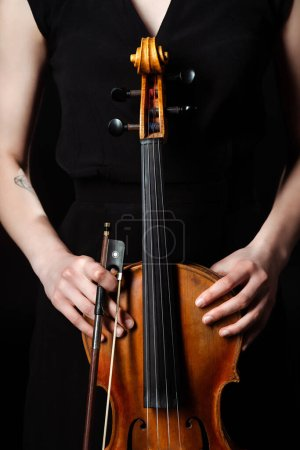 Photo for Cropped view of female musician holding classical violin on dark stage - Royalty Free Image