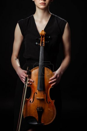 cropped view of female musician holding classical violin isolated on black