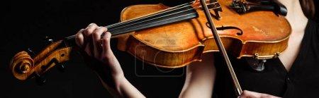 Photo pour Vue partielle d'une musicienne jouant sur violon isolé sur noir, image horizontale - image libre de droit