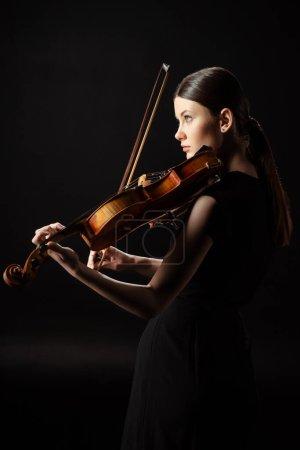 Photo pour Jolie musicienne jouant sur violon isolé sur noir - image libre de droit