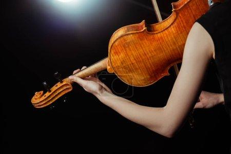 Photo pour Vue recadrée d'une musicienne professionnelle jouant du violon sur scène sombre - image libre de droit