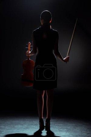 Photo pour Silhouette de musicienne tenant violon sur scène sombre - image libre de droit