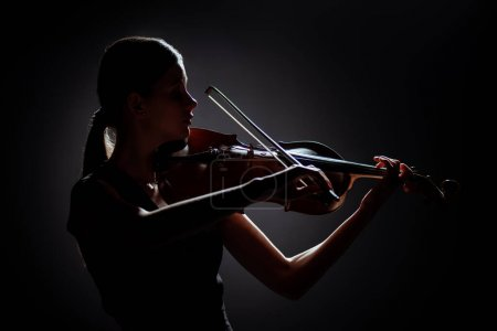 Photo for Silhouette of professional musician playing on violin on dark stage - Royalty Free Image
