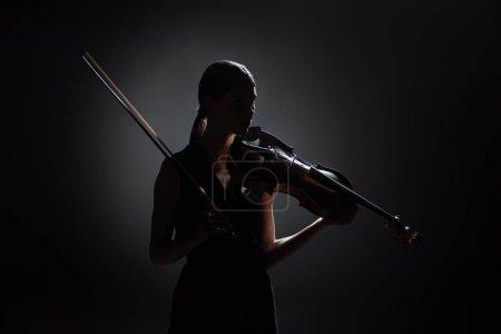 Photo pour Silhouette de musicienne professionnelle jouant du violon sur scène sombre - image libre de droit