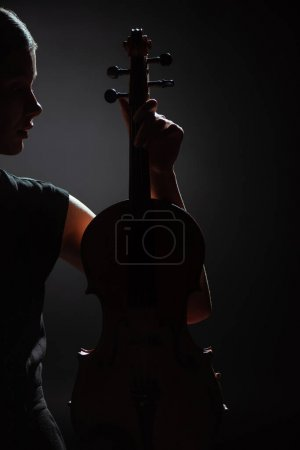 Photo for Silhouette of female musician holding violin on dark stage - Royalty Free Image