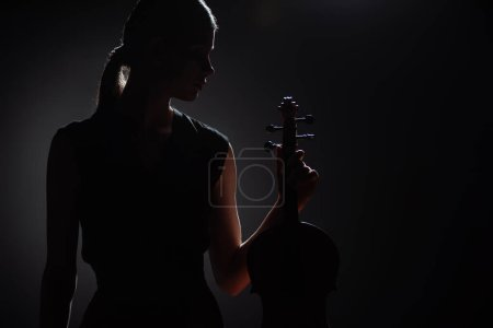 Photo pour Silhouette de musicienne tenant un violon classique sur scène sombre - image libre de droit