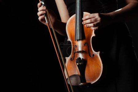 Photo pour Vue partielle du musicien tenant le violon isolé sur noir - image libre de droit
